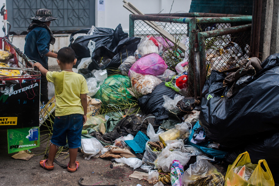 A child watches as his mother picks through waste in Sathom District, Bangkok, Thailand. June 2015.  Nearly one-third of the 6.6 million under-5 child deaths every year are associated with environment-related causes and conditions. Environmental risk factors often act in concert, and their effects are exacerbated by adverse social and economic conditions, particularly conflict, poverty, and malnutrition.  Illustration about Children's Environmental Health in Thailand.