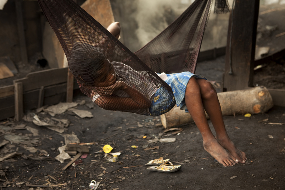 Hidden cities is a joint WHO / UN-HABITAT report about urbanization and global health issues. Photo stories from around the world reflect the hidden realities urban dwellers are facing, and highlight some health inequities.  A girl in a hammock next to the coal fires on the street in Tondo, Manila, Philippines