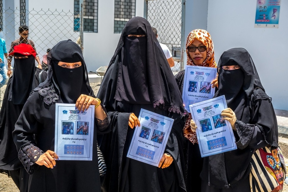 A group of local health workers hold up guidebooks intended for health personnel during WHO's Oral Cholera Vaccination campaign in Aden, Yemen.