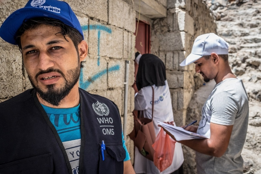 A WHO staff health worker goes door to door with two local health workers during WHO's Oral Cholera Vaccination campaign in Aden, Yemen.