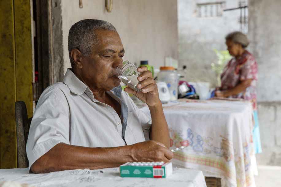 Daniel Lordelo Vaz, aged 77, taking his diabetes medications while his wife Maria Filomena, aged 73, stands in the background. The couple lives with family relatives in Leandrinho, Dias D'Àvila, Bahia, Brazil.