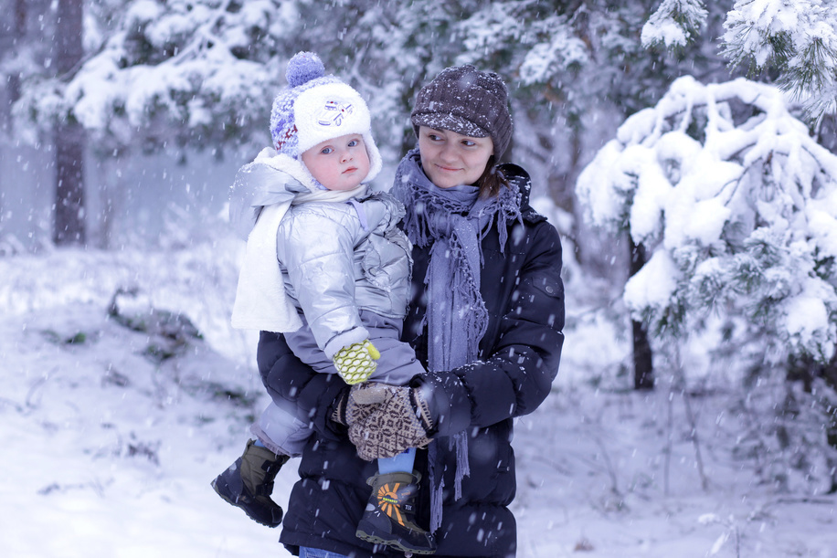 A young mother with her child in a park in winter, Moscow, Russia.  Illustration about child and maternal health in Russia