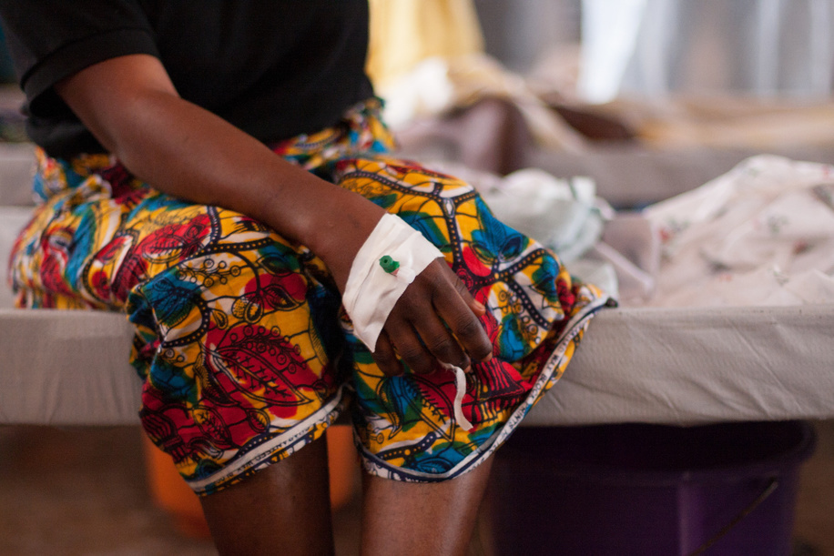 """A female patient sitting on a bed at the Wellington Cholera Treatment Centre in Freetown, Sierra Leone.  A cholera outbreak in Sierra Leone has killed almost 300 people and affected more than 20 000. Without support to expand and sustain the response operation, as many as 32 000 cases could be expected this year. The World Health Organization (WHO) and the Ministry of Health and Sanitation have established a cholera control and command centre to coordinate the response to what has turned into a national emergency. WHO has brought in experts in epidemiology, surveillance, case management, logistics, social mobilization, water and sanitation from other WHO offices as well as from the International Centre for Diarrhoeal Disease Research, Bangladesh, and the United Kingdom's Health Protection Agency. Much of the work being done by WHO and partners will help to strengthen the country's capacity to deal with disease outbreaks in the future. However WHO Representative in Sierra Leone Dr Wondimagegnehu Alemu warns that there is an urgent need for investment in infrastructure to improve safe water supply and sanitation. """"Water and sanitation is going to remain a long-term challenge, particularly in the slums in Freetown where people are at high risk of diarrhoeal disease,"""" he says. By 27 September 2012, reports of cholera cases were continuing to decrease and the death rates had reduced to less than 1% of cases in 3 out of the 12 affected districts. Some cholera treatment units in Freetown operated by nongovernmental organizations have closed due to reduced cases. However, in the recently affected districts, new cases are still coming in and work must continue to control the outbreak and prevent further deaths from this treatable disease."""