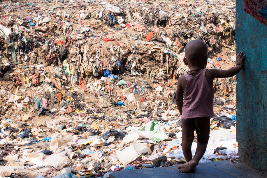 Young child looking out at the mountains of waste. Shivaji Nagar, Deonar, Mumbai. March 2015.  Nearly one-third of the 6.6 million under-5 child deaths every year are associated with environment-related causes and conditions. Environmental risk factors often act in concert, and their effects are exacerbated by adverse social and economic conditions particularly conflict, poverty, and malnutrition.  Illustration about Children`s Environmental Health in India.