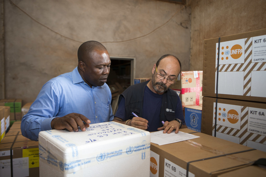 Luis Cremades (right), WHO logistician, organizes the handover of a donation of medicines and medical supplies to a local NGO at the WHO warehouse in Bangui, Central African Republic. After an increase in violence in the country and the internal displacement of more than 200,000 people, access to essential health care for many people has become limited.  Title of WHO staff and officials reflects their respective positions at the time the photo was taken.