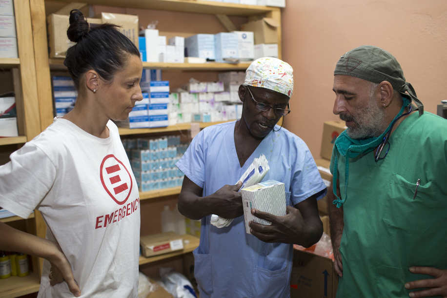 Dr Ombretta Pasotti, EMERGENCY Medical Coordinator and Head of Mission, Abraham Marotso, Operating Theatre (OT) nurse, and Dr Enrico Pacanelli, orthopediatric surgeon at a Bangui hospital, in conversation at EMERGENCY's supply room. This nonprofit organization is a WHO partner in Central African Republic and receives medical supplies from WHO warehouse.  After an increase in violence in the country and the internal displacement of more than 200,000 people, access to essential health care for many people has become limited.