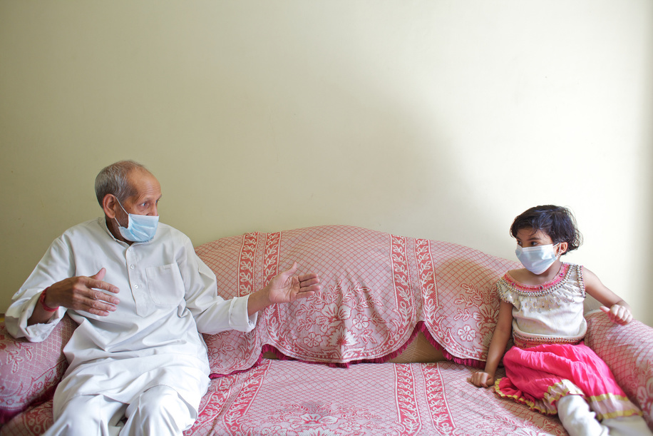 This series focuses on different aspects of having influenza in India.  A man and his granddaughter wear face masks while sitting a distance apart from each other in a middle class household of north Delhi.