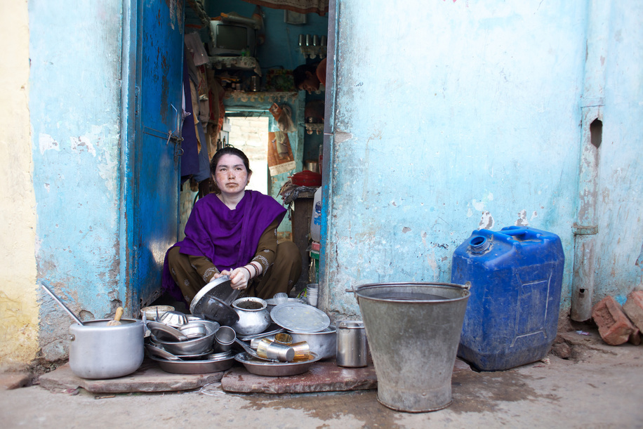 This series focuses on different aspects of having influenza in India.  A woman washes cooking pots and pans outside her home in a Delhi slum.
