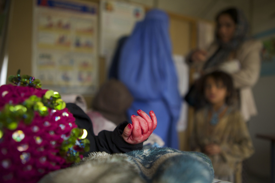 Shamsullah, aged 5 months and suffering from a cold, lies on a bed at a mobile clinic sponsored by WHO at the Charah-e-Qambar refugee camp in Kabul, Afghanistan.