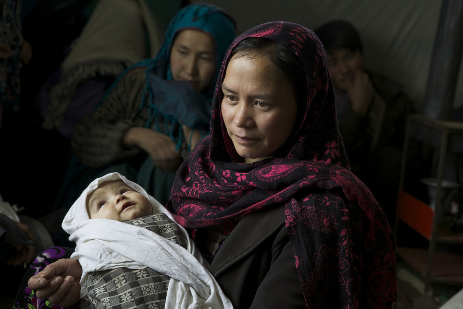 Fatima, aged 30 and mother of 5 children holds her child of 10 months, Hania, while waiting  to be examined at a mobile clinic facilitated by WHO in the Kaj Nāw village located in the Panjab district in Bamiyan, Afghanistan.