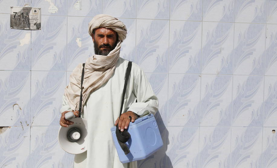 A vaccinator carrying vaccine carrier and a loudspeaker poses for a picture in the field as they go mouth by mouth, house by house in every street to vaccine children under five years old in Kandahar tense province of Afghanistan, 02 Sep 2016. WHO/JAWAD JALALI