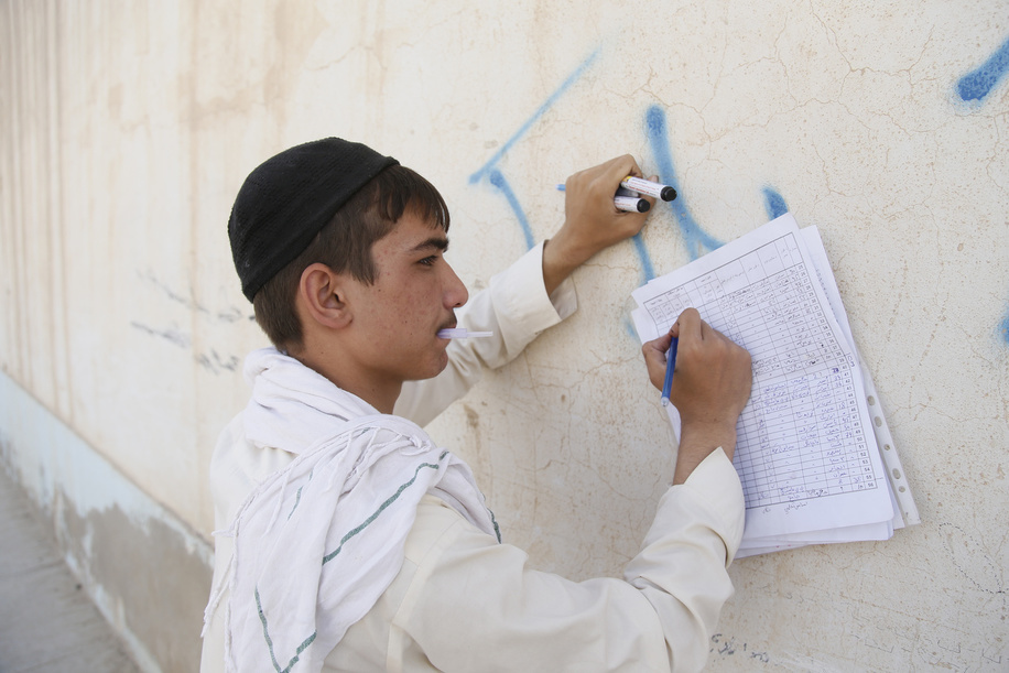 Polio vaccination campaign in Afghanistan.  A volunteer vaccinator tally his absentees list as they follow up with absent children in the field where they go mouth by mouth, house by house in every street to vaccine children under five years old against Polio.