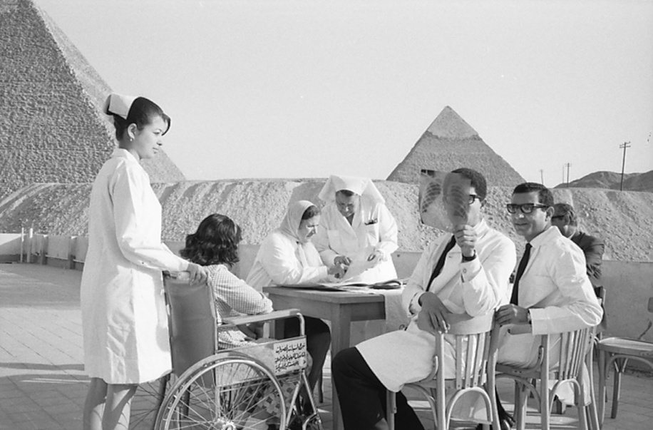 The incidence of heart and joint disabilities resulting from rheumatic fever was indeed high in the United Arab Republic, especially among the poorer classes. This was particularly true in those regions where population density and overcrowding encourage the spread of streptococcal infection.  On the terrace of the hospital. At the table in the background, Dr Zahira Abdine, Directress of the clinic, examines the file of a young patient.