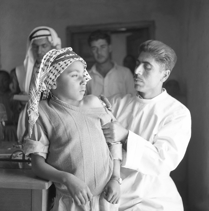 Mr Nicola Awad, vaccinator, is giving BCG to a boy in rural school of Dayat village.  c. 1950 - c. 1959