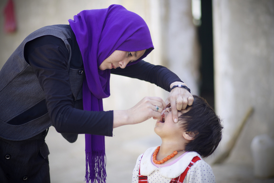 Tahera, 24, who works as a volunteer vaccinator administers polio vaccine drops to a child during the first day of a polio vaccination campaign in Bamyan on October 17, 2016.