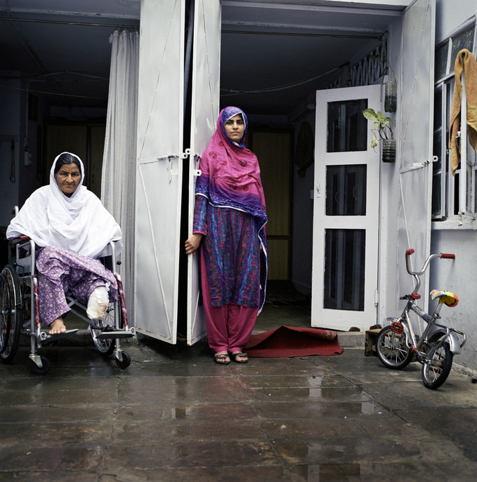 Zahida Bibi (left), 65, sits on a wheelchair with a female family member by her side. This particular feature presents Zahida, who has had diabetes for the past 20 years. For years, she did not know that she had the disease.
