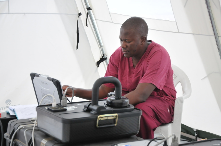Ebola Outbreak in Liberia - WHO and partner's response to Ebola virus disease (EVD) outbreak in Liberia.  Field mobile laboratory near ELWA 3 treatment facility is supported by CDC and WHO GOARN (Global Outbreak Alert and Response Network).  CDC staff monitors test results on a computer.
