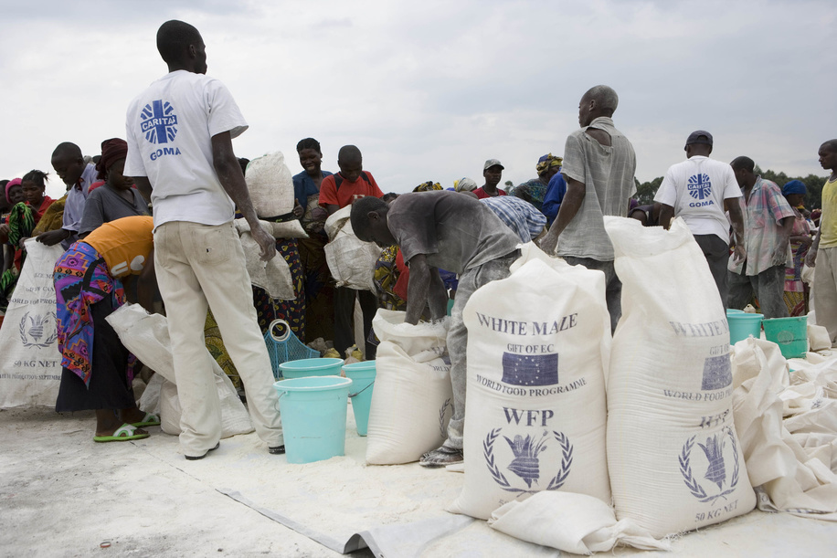 Feature about Internally Displaced People (IDP) due to conflicts in Democratic Republic of the Congo.  Bags of white maize from WFP (World Food Program) and distribution.