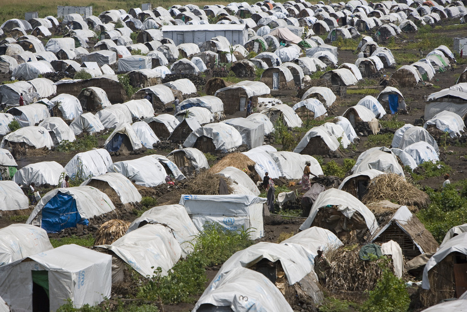 Feature about Internally Displaced People (IDP) due to conflicts in Democratic Republic of the Congo.  A view of the camp at Buhimba - rudimentary houses covered with a white tarpaulin in a field.