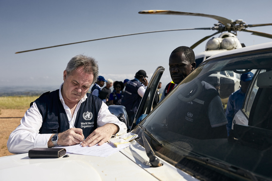Director of the Wellcome Trust and Chair of WHO's Research and Development Blueprint Dr Jeremy Farrar takes notes before getting on a helicopter in Komanda, Ituri province, on 02 January 2019. Komanda is one of the current epicentres of the ongoing Ebola outbreak.  Dr Tedros traveled over the New Year to Ebola-affected areas in the DRC to review the response at this critical phase. On the three-day mission (31 December 2018 - 2 January 2019) to Beni, Butembo and Komanda, Dr Tedros took stock of the outbreak, spent time with affected communities, and personally thanked responders for their dedication. WHO has 380 response staff in North Kivu and Ituri working together with hundreds more from the Ministry of Health and partners.   Title of WHO staff and officials reflects their respective position at the time the photo was taken.