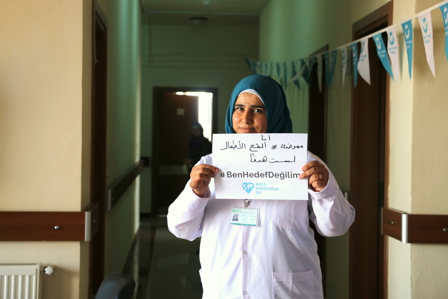 World Humanitarian Day 2017 - I am a nurse. I vaccinate children. I am not a target. Protect Health Workers. #NotATarget #ProtectHealthWorkers - In December 2008, the sixty-third session of the UN General Assembly decided to designate 19 August as World Humanitarian Day. 19 August is the date on which a brutal terrorist attack on UN headquarters in Baghdad in 2003 killed 22 people, including UN envoy Sergio Vieira de Mello. 2017 WHD campaign: #NotATarget Conflict is taking a massive toll on people's lives around the world. Trapped in wars not of their making, millions of civilians are forced to hide or run for their lives. Children are taken out of school, families are displaced from their homes and communities are torn apart. At the same time, health workers and aid workers - who risk their lives to care for people affected by violence - are increasingly being targeted. But the world is not doing enough to end their suffering. Source: https://www.unocha.org/world-humanitarian-day-2017 - Caption was not provided by the photographer. Therefore, a generic caption has been applied to this image.