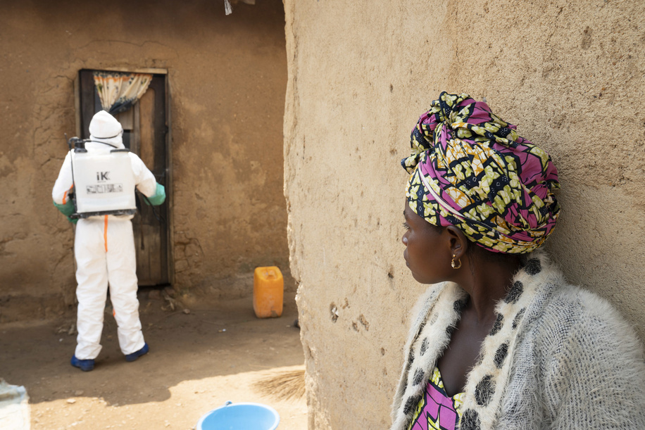 WHO's response to Ebola virus disease (EVD) outbreak in the Democratic Republic of Congo.  A family member watches as the house of person who recently died of Ebola is disinfected.