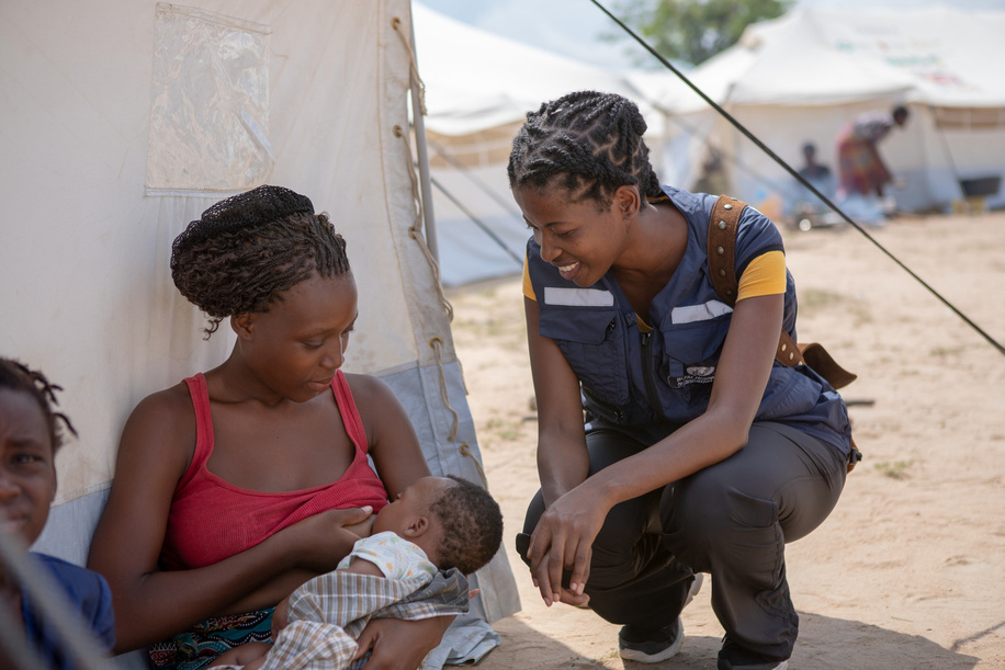 Woman breastfeeding a baby while waiting to receive support at the Samora Machel accommodation center in Dondo following Cyclone Idai devastation.   WHO and partners are supported local health services for ongoing needs, including pregnancy care, malnutrition screening, and plans for child health interventions including deworming, vitamin A supplements, and measles vaccination during the emergency campaign.