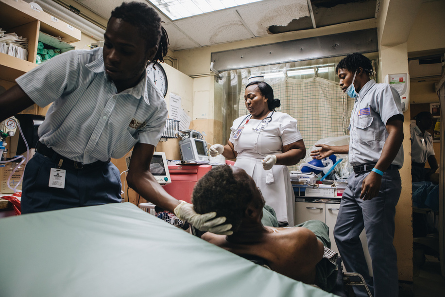 2020 Year of the Nurse and Midwife.  Porters move an unconscious patient onto a stretcher as Trecia Simone Stewart, 41, a certified emergency nurse prepares for the patient's intake at Spanish Town Hospital.  - Read the story: https://www.who.int/news-room/feature-stories/detail/emergency-nursing-in-jamaica