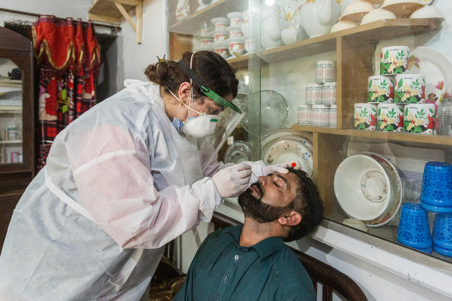 Dr Samreen Khalil, WHO Polio Eradication Officer, collects a sample from Muhammad Shabir at his residence in order to test for COVID-19. - Title of WHO staff and officials reflects their respective position at the time the photo was taken.