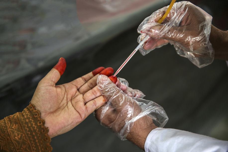 Lal Mohammad, a lab technician conducts a hemoglobin test of a pregnant woman in basic health unit Akora II, Nowshera District, Khyber Pakhtunkhwa province, Pakistan. Photographer: Asad Zaidi