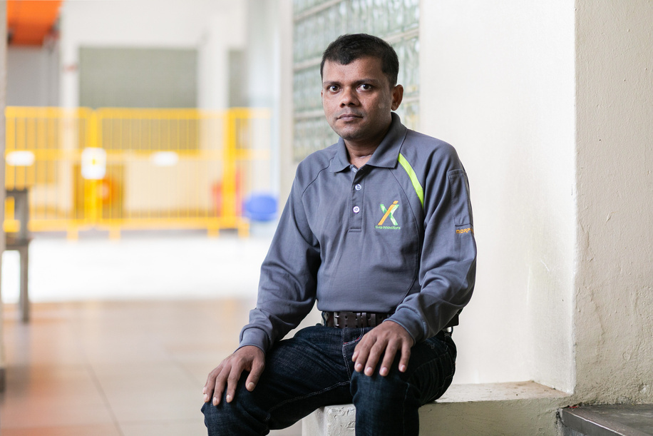 """COVID-19: SINGAPORE  Singapore's COVID-19 response is a collective effort of stakeholders from businesses, the community, and government. This includes working together with non-governmental organizations and more than 5000 migrant ambassadors who can engage with the migrant worker communities in their own languages.  Raju Sarker poses for a portrait at the dormitory where he lives in Singapore. Raju is a migrant worker from Bangladesh. He contracted COVID-19 and recovered after receiving medical care. """"Actually I could not feel when the disease came or when it left. I only remember going to the hospital with a cough and cold, but what happened after that, when and how I was treated, I don't know anything. It is only after I regained consciousness that I found out that I had contracted the disease and after that I suddenly received the news of my son's birth. With the help of the doctor's cell phone, I saw my son's photograph. After looking at my son I was filled with courage and joy. He gave me the inspiration and courage to survive, and the will to live."""""""