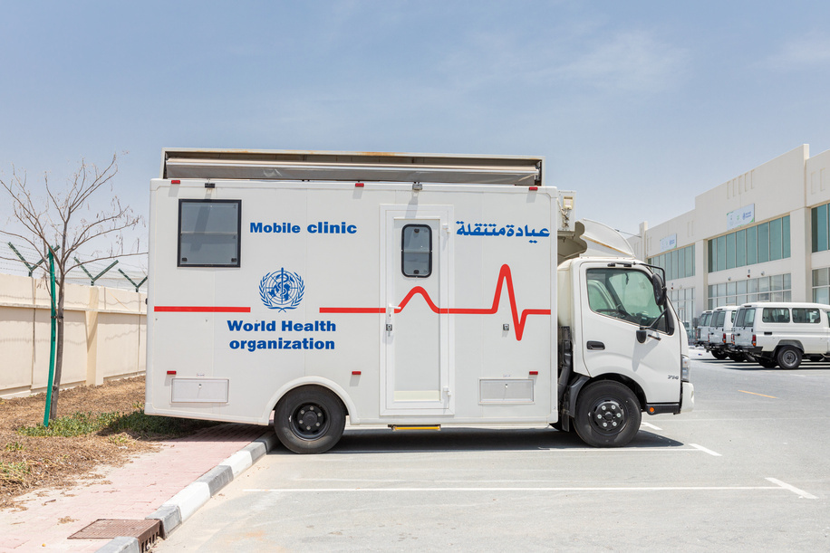 A mobile clinic outside the WHO warehouses in Dubai.   The World Health Organization's Health Emergencies Programme maintains a Logistics hub located within the International Humanitarian City in Dubai. The WHO/Dubai operation maintains over 17,000 square meters of temperature-controlled warehousing and manages an inventory of medicines, medical supplies, and equipment valued at USD 40 million. The operation provides support to health emergencies across the globe in response to all types of events ranging from natural disasters to outbreaks of infectious disease. Since the start of the COVID-19 pandemic, the WHO/Dubai operation has expanded to over 4 times its original size and has completed over 324 shipments to 108 destinations across all 6 WHO geographic regions.   With the implementation of a WMS (warehouse management system) including bar-coding and scanning, the operation will gain significant efficiencies in managing inventory and rapidly dispatching supplies. The Operation established a dashboard to increase the visibility of supply chain data to support the tracking and monitoring of medical supplies dispatched from the logistics hub. Most recently, in response to the blast in Beirut, Lebanon the operation responded within 24 hours by delivering over 20 metric tons of trauma and surgical supplies; clearly demonstrating the rapid response capability and advantages of maintaining a pre-positioned supply of critical medical supplies and equipment.