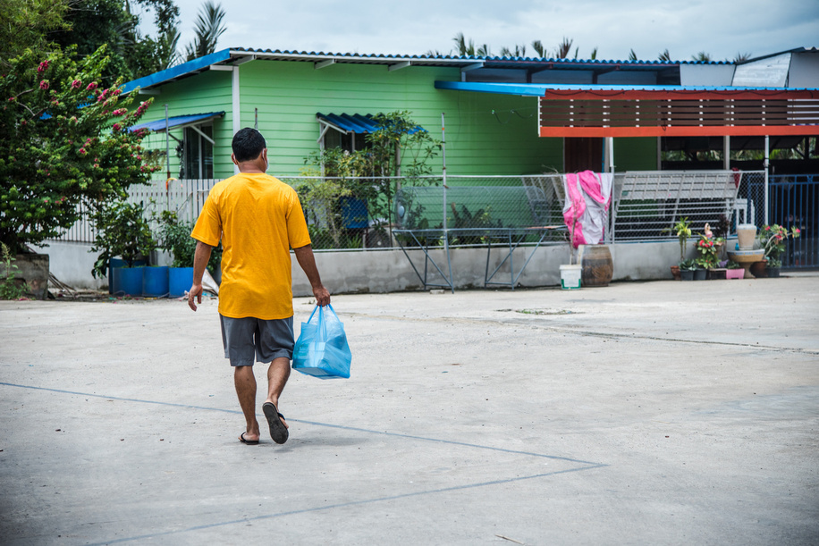 A Burmese dormitory caretaker walks towards the dorms where migrant workers live in Samut Sakhon Province, on 17 June 2020. Thai officials are working to prevent any COVID-19 outbreak in the dorms.