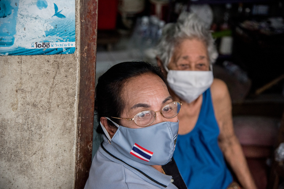 A health volunteer (foreground) and her patient (background) during a home visit on 23 September 2020, in Bang Phut Sub District.