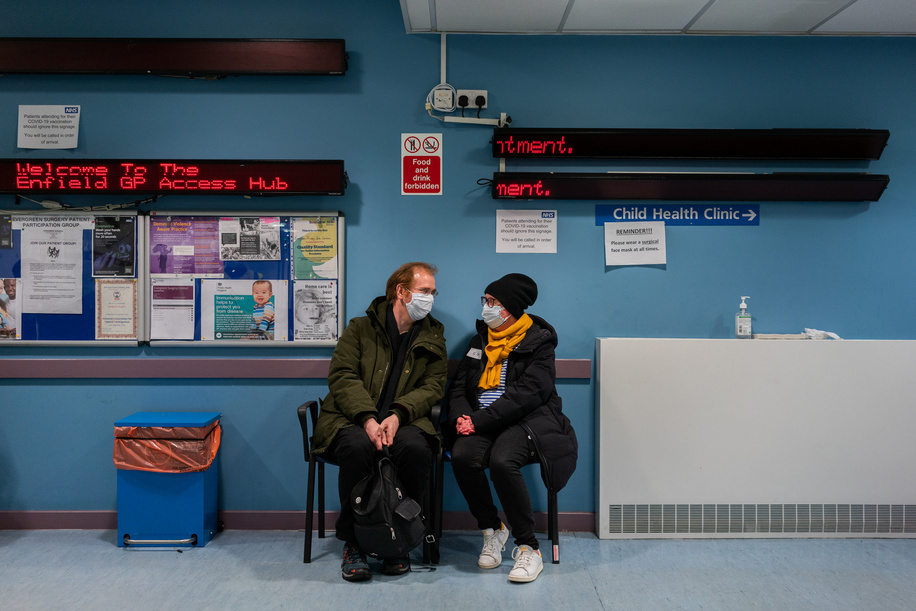 Phoebe Harkins (right), 51, waits to be called in to receive a COVID-19 vaccine at Evergreen Primary Care Centre in the London borough of Enfield in the United Kingdom of Great Britain and Northern Ireland, on 24 January 2021. She is very happy to be vaccinated.