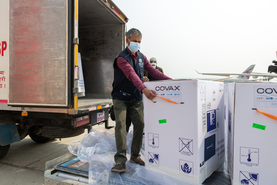 On 7 March 2021, WHO Nepal Operations Support & Logistics Officer Prahlad Dahal takes a look at Nepal's first consignment of COVID-19 vaccine doses via COVAX as they are loaded onto a truck at Tribhuvan International Airport in Kathmandu.  COVAX, the vaccines pillar of the Access to COVID-19 Tools (ACT) Accelerator, is co-led by the Coalition for Epidemic Preparedness Innovations (CEPI), Gavi, the Vaccine Alliance Gavi) and the World Health Organization (WHO) Ð working in partnership with developed and developing country vaccine manufacturers, UNICEF, the World Bank, and others. It is the only global initiative that is working with governments and manufacturers to ensure COVID-19 vaccines are available worldwide to both higher-income and lower-income countries.  Title of WHO staff and officials reflects their respective position at the time the photo was taken.