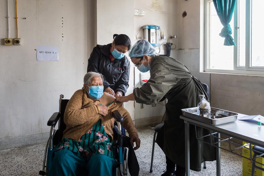 On 12 March 2021, Saraswoti Devi Shrestha (left) receives COVID-19 vaccine at Paropakar Maternity and Women's Hospital in Kathmandu, Nepal.