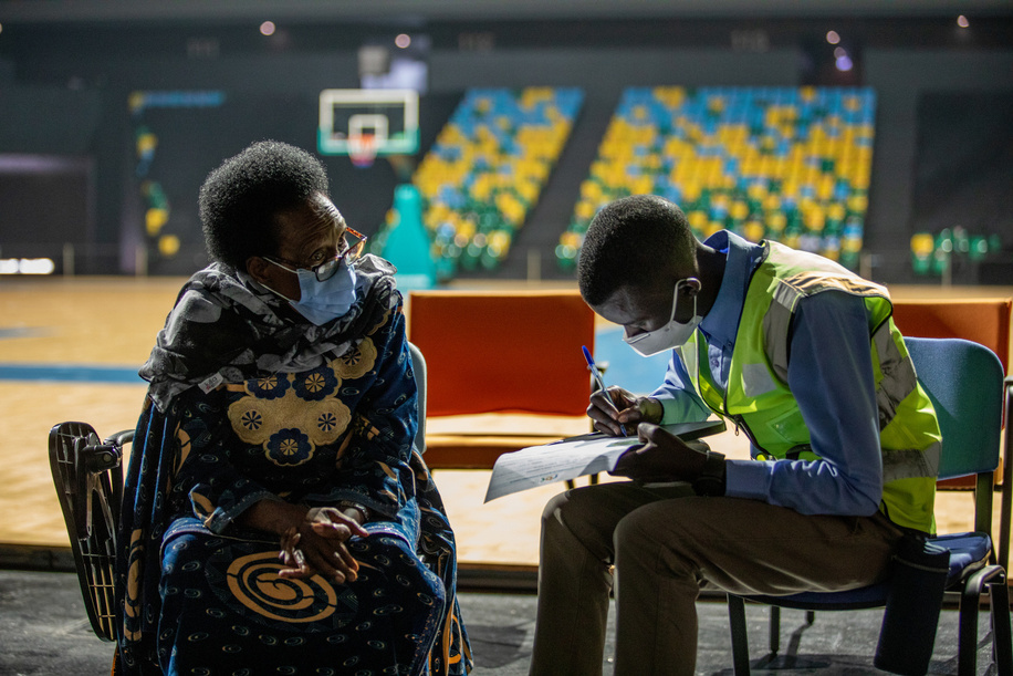 On 5 March 2021, a volunteer helps a woman fill out paperwork before her COVID-19 vaccine in Rwanda. COVAX, the vaccines pillar of the Access to COVID-19 Tools (ACT) Accelerator, is co-led by the Coalition for Epidemic Preparedness Innovations (CEPI), Gavi, the Vaccine Alliance Gavi) and the World Health Organization (WHO) working in partnership with developed and developing country vaccine manufacturers, UNICEF, the World Bank, and others. It is the only global initiative that is working with governments and manufacturers to ensure COVID-19 vaccines are available worldwide to both higher-income and lower-income countries.