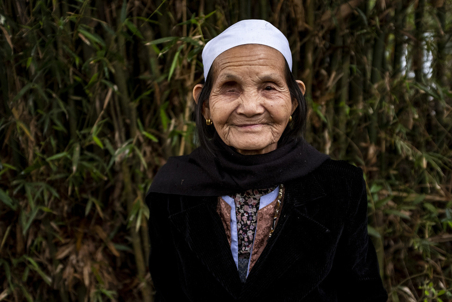 Hoa Binh City - 13 March, 2018: Portrait of Mrs. Dinh Thi Nguyen, 80 in her way to the house of her friend Mrs. Trieu Thi Mui, 87 after the yearly eye revision day at Thong Nhat Commune Health Center in Hoa Binh City in Northern Vietnam. They are friends since the year 1954. Every year around 100 elderly people from the Thong Nhat Commune attends the local Health Center to do a screening of their vision. Mrs. Dinh Thi Nguyen had the right eye removed because of glaucoma; and in the left one she has serious cataract. She will be transferred for a cataract operation to the the Vietnamese National Institute of Ophthalmology (VNIO) in Hanoi.Mrs. Dinh Thi Nguyen husband died 3 years ago and currently she lives in a farm with her extended family in Thong Nhat Commune in Hoa Binh City. She is from the Muong ethnic minority.
