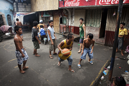 Hidden cities is a joint WHO / UN-HABITAT report about urbanization and global health issues. Photo stories from around the world reflect the hidden realities urban dwellers are facing, and highlight some health inequities.  Young men play basketball in Parola, Manila, Philippines.