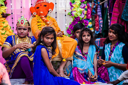 Young girls sitting together with a person wearing an elephant mask during celebrations of the Shivaratri Festival in the city of Pushkar. The elephant mask represents Ganesha, a deity in the Hindu pantheon. Illustration about Shivaratri Festival in Pushkar, India. February 2015
