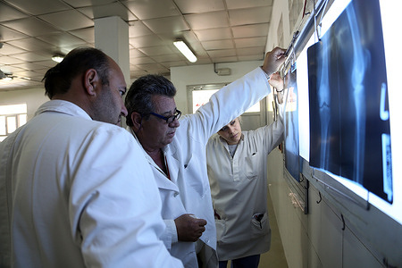 Emergency Hospital in Afghanistan.  Chiara Lodi Italian doctor (R) Dr Carlo (C) and Dr Qudos (L) look at Xray photo of a patient at Emergency hospital in Lashkargah.