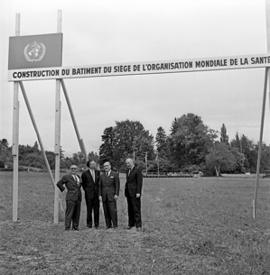 """The WHO Headquarters, just outside of Geneva, was built from 1962 to 1966. Jean Tschumi (1904-1962) of Lausanne, Switzerland, was the architect of the building.It is a concrete structure of 150 metres long, 20 metres wide, and 34 metres high supported by 22 columns.  The foundation stone of the new Headquarters building of the World Health Organization was laid during a ceremony held on the 24th of May 1962 on the building site """"En Choutagnes"""", at Pregny, on the outskirts of Geneva. Present at the ceremony were representatives of the Swiss Federation and the City and Canton of Geneva, the delegates to the Fifteenth World Health Assembly (representing the 115 Member and Associates Member States of WHO) and representatives of the United Nations and various international bodies with headquarters in Geneva. On the building site, from left to right: M. Joseph Handler, Director of Public Information of WHO; Dr Pierre Dorolle, Deputy Director-General of WHO; Dr Marcolino G. Candau, WHO Director-General; Dr Rodolphe Coigney, WHO Protocole Officer. - Title of WHO staff and officials reflects their respective position at the time the photo was taken."""