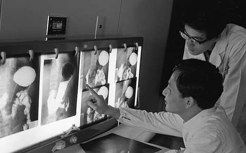 A doctor examining the X-ray of a patient, who is also to be photographed by gastro camera.