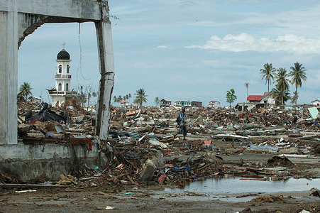 A man picks his way through the wholesale destruction wrought by the tsunami in downtown Banda Aceh. A single minaret from a mosque remains standing amidst the ruins.  The tsunami on December 26, 2004 devastated the city of Banda Aceh and the west coast of Sumatra. The fear of disease was acute as the region headed into the rainy season. Tens of thousands were left homeless and living in makeshift shelters, while tens of thousands of corpses were strewn in the streets. WHO was central to the coordination of health aid and organising the deployment of a Rapid Health Assessment (RHA) Team. The RHA, which is comprised of different agencies, identified the basic needs of the affected populations that required immediate response. The coordination efforts of the WHO and partner agencies were vital in addressing significant threats to public health in the devastated areas, especially water-borne diseases. Priority initiatives included the construction of emergency shelters and mobile clinics, distribution of food aid, performance of environmental health interventions, and an assessment of the long term needs of orphans.