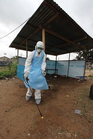 WHO Ebola response interventions in Liberia in September 2014.  Health worker wearing protective equipment (PPE) disinfecting.
