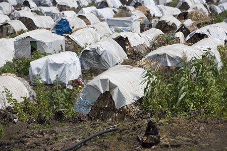 Feature about Internally Displaced People (IDP) due to conflicts in Democratic Republic of the Congo.  A woman sits in front of rudimentary houses covered with a white tarpaulin in a field.