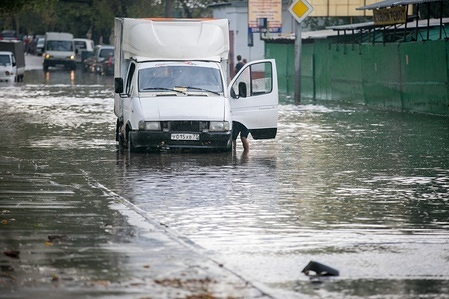 Illustration about environmental issues in Russia  Cars are trying to move forward in a flooded street, Moscow, Russia.