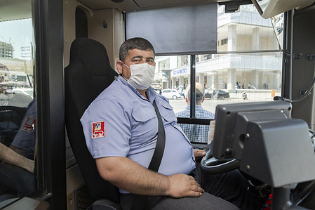 A bus driver in Baku, Azerbaijan.   Public information is widely seen on billboards, posters and public transit. People displaying a variety of protective behavior and equipment move about the city.