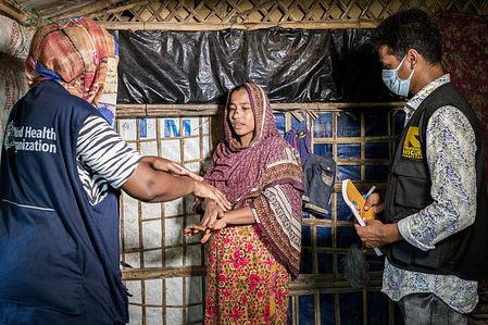 COVID-19: BANGLADESH  WHO is supporting COVID-19 preparedness and response for vulnerable Rohingya refugees and host communities in Cox's Bazar, Bangladesh. WHO assisted the IEDCR (Institute of Epidemiology Disease Control And Research) Field Laboratory in Cox's Bazar to increase COVID-19 testing capacity from around 100 tests per day to over 1500 per day. WHO also mobilized partners to establish over 1000 beds in and around the camps for treatment of severe cases of COVID-19. In addition, WHO is enhancing the disease surveillance system, strengthening contact tracing, training health workers on infection prevention and control, and delivering essential health supplies.  WHO Infection Prevention and Control Specialist Rebecca Rachel Apolot (left) and IRC volunteer, Tarekul Islam (right) visit Romida Begum and her family in a Rohingya refugee camp to explain how to reduce the risk of COVID-19 infection. - Title of WHO staff and officials reflects their respective position at the time the photo was taken.